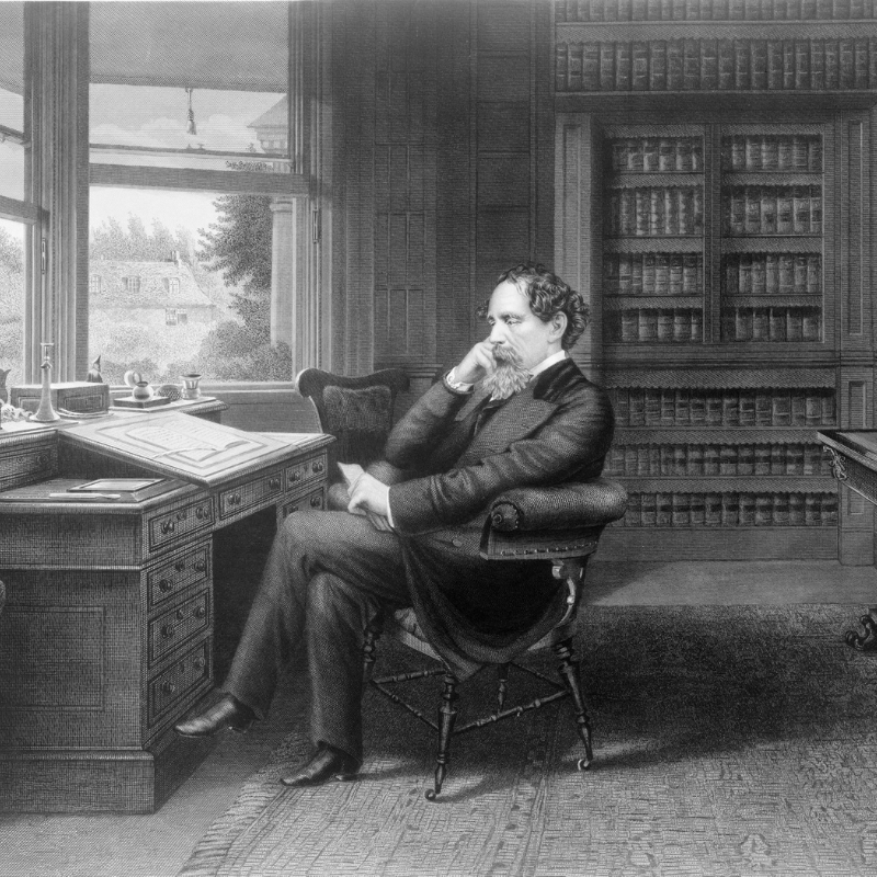 Charles Dicken sitting at his writing desk